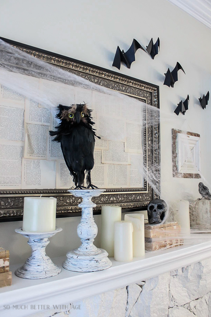 Black crows, bats, candles and spider web on the fireplace mantel.