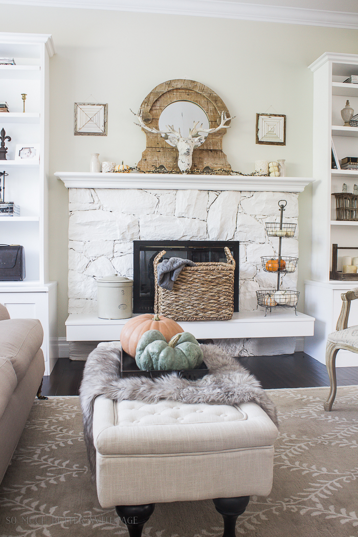White fireplace with wire basket full of pumpkins beside it and pumpkins on ottoman.
