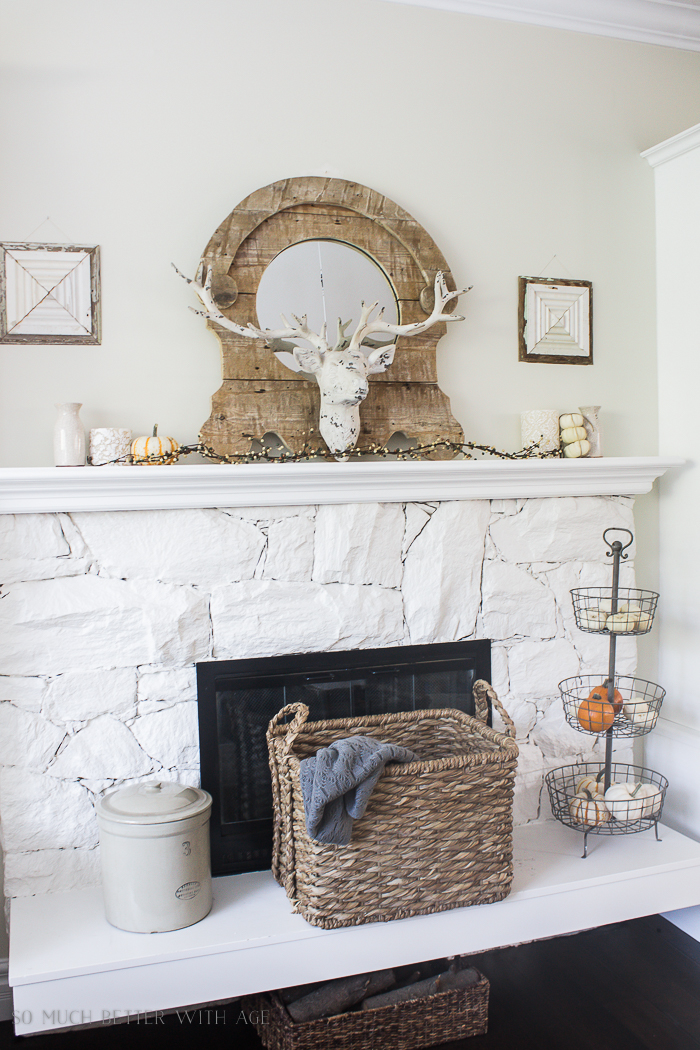 Deer antlers, branches and pumpkins on mantel.