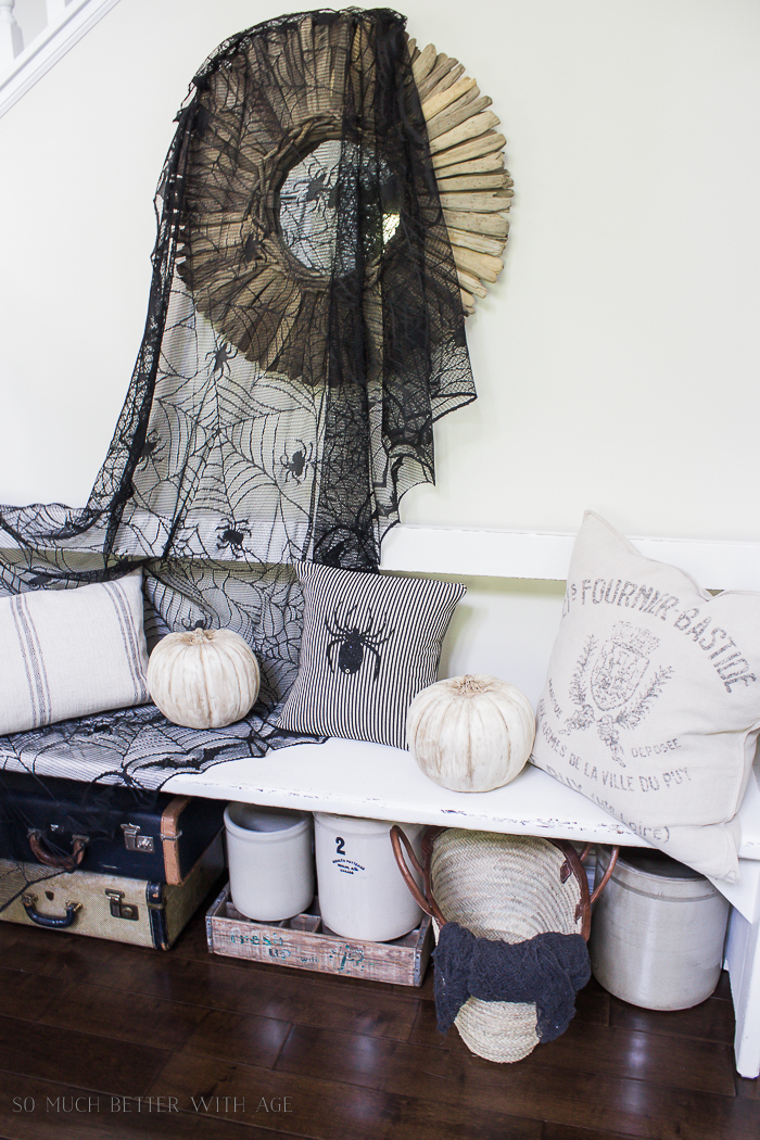 Halloween spider pillow, and spider black netting hanging above bench.