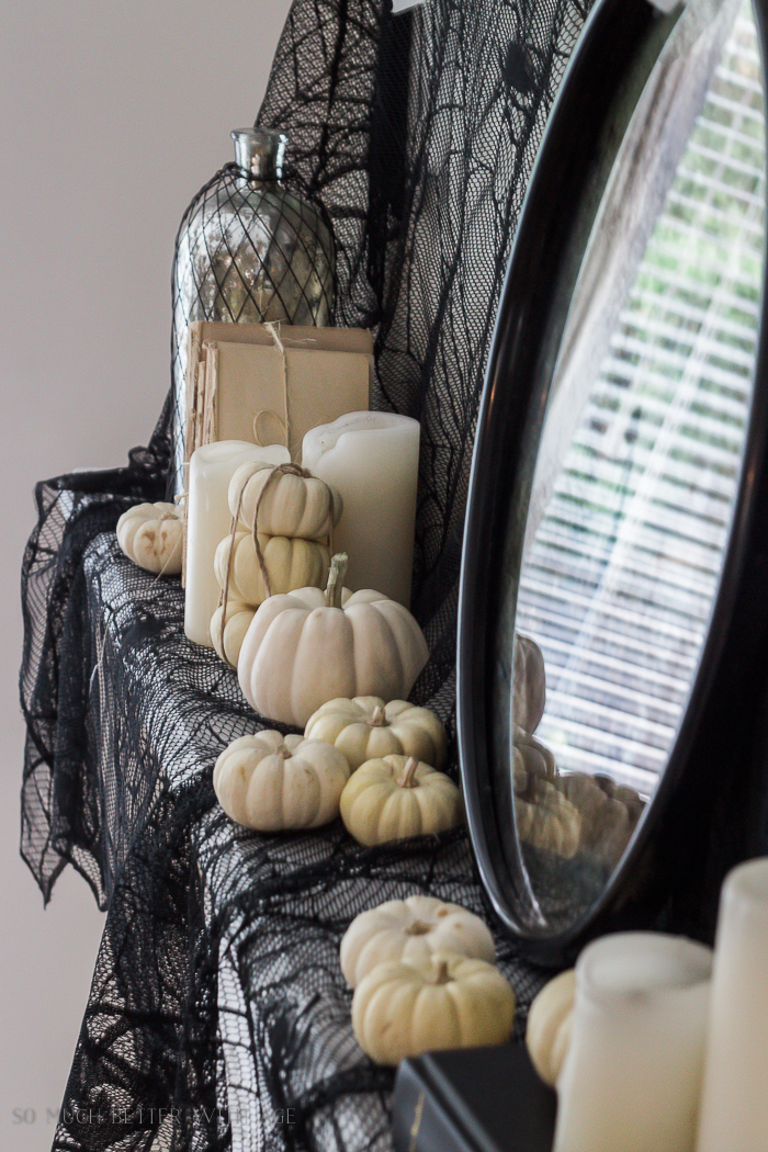 Black netting and baby pumpkins on the mantel.