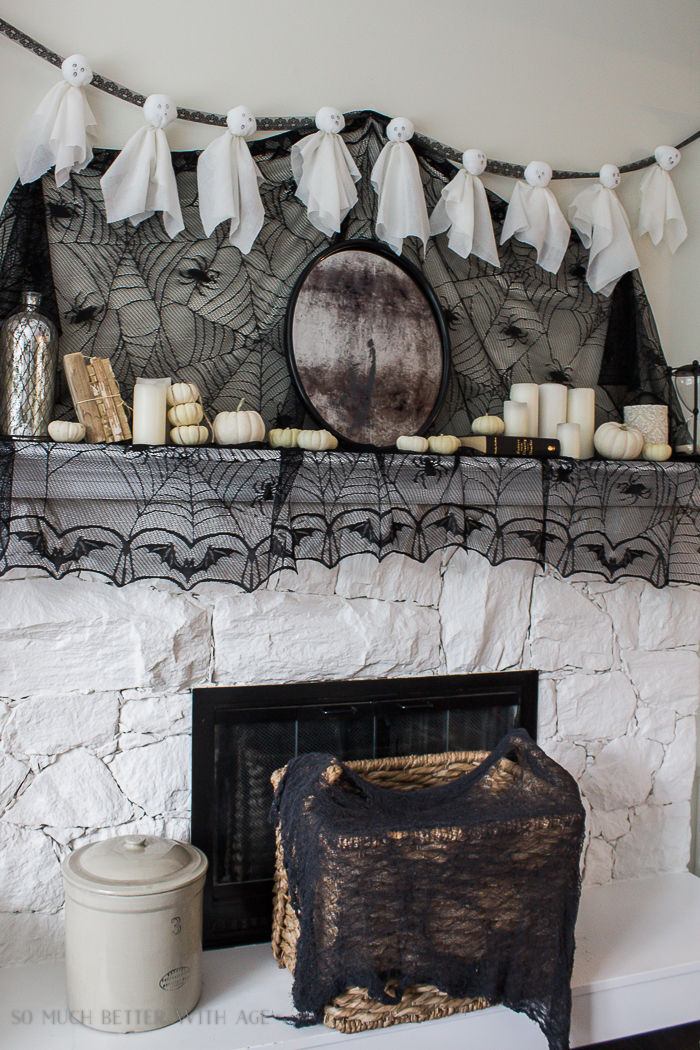 White ghosts hanging on the mantel with black netting.
