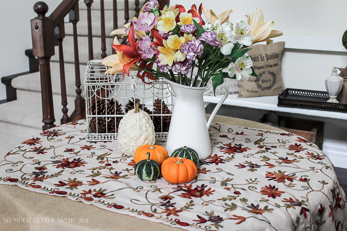 Floral tablecloth, white pitcher filled with multi coloured flowers, and small pumpkins on hallway table.