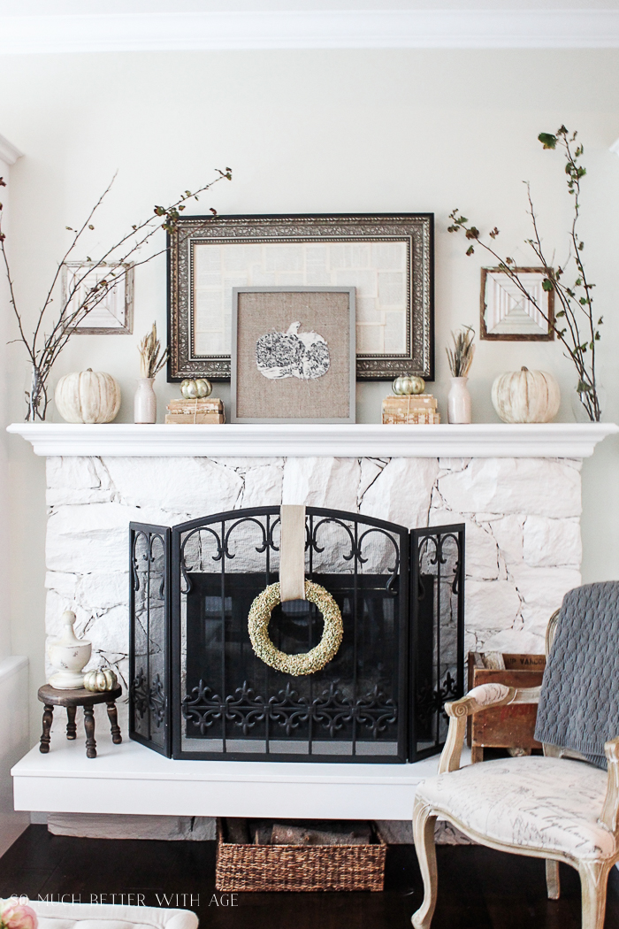 White fireplace mantel decorated with vintage books, pumpkins, branches, and vintage mirror.