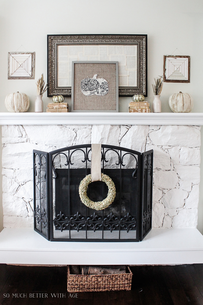 Split pea wreath hanging on the fireplace with pumpkin picture on the mantel.