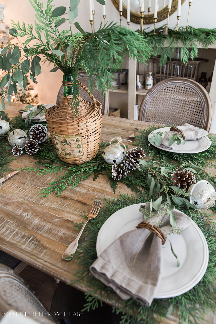 A French wicker jug with eucalyptus and evergreen in it, as a centrepiece in the middle of the table.