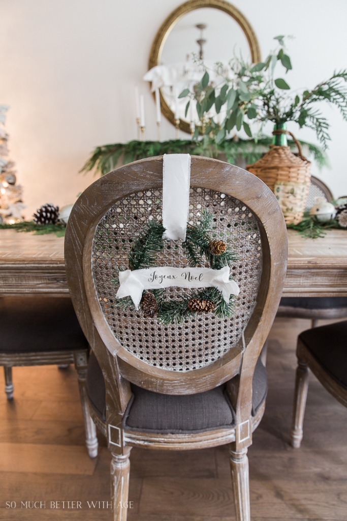 Mini Christmas wreath on back of cane dining chair.