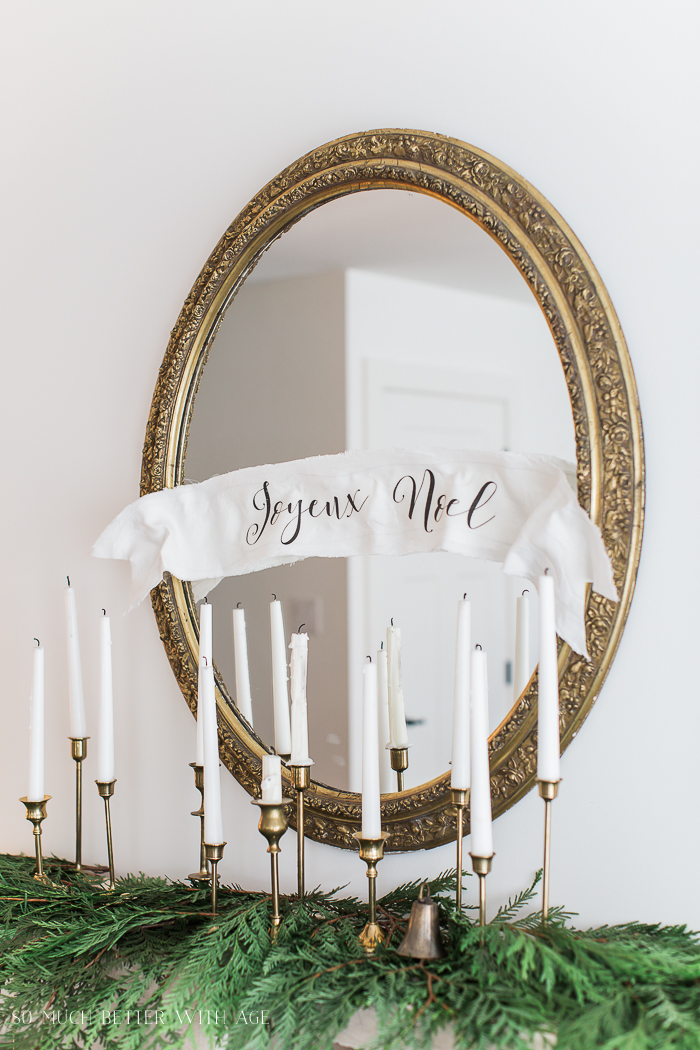 French gold mirror and white candles on mantel.