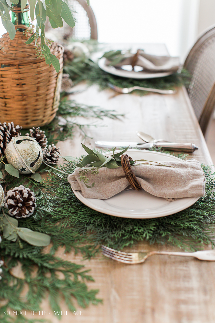 Neutral linen napkins with wooden napkin holder and a sprig of eucalyptus.
