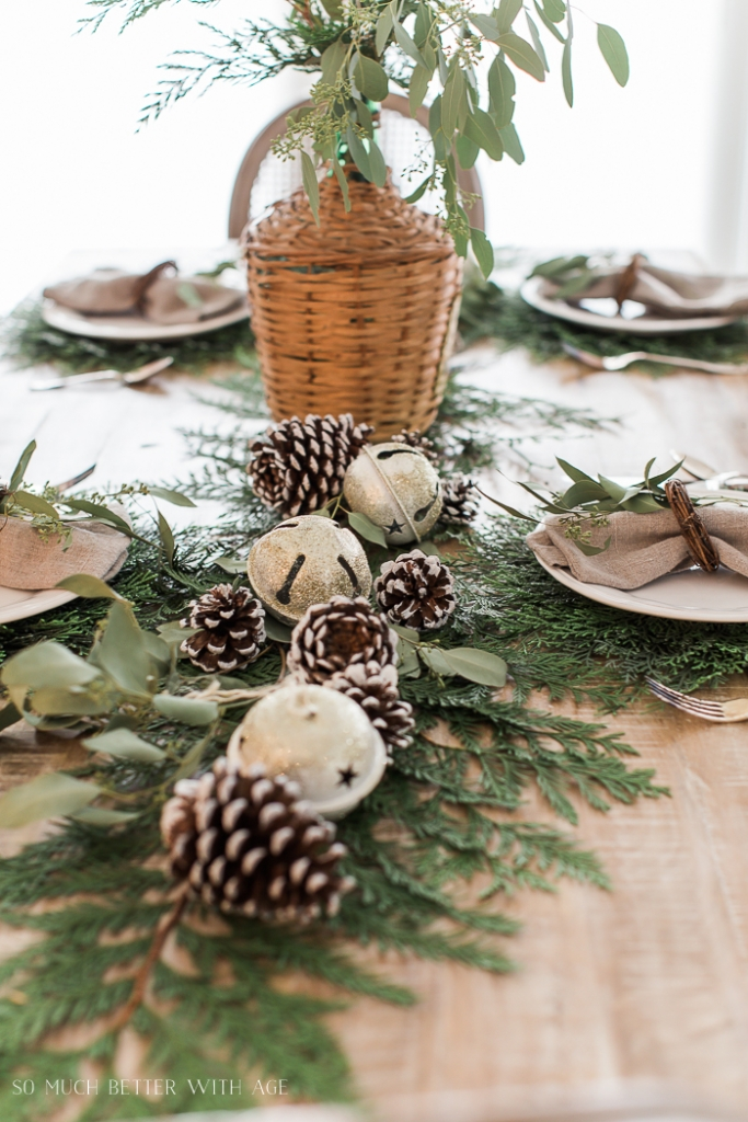 Christmas table with evergreen and pinecones.