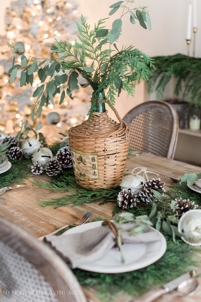 Evergreen, pinecones and an olive container with greenery on the table set for Christmas.