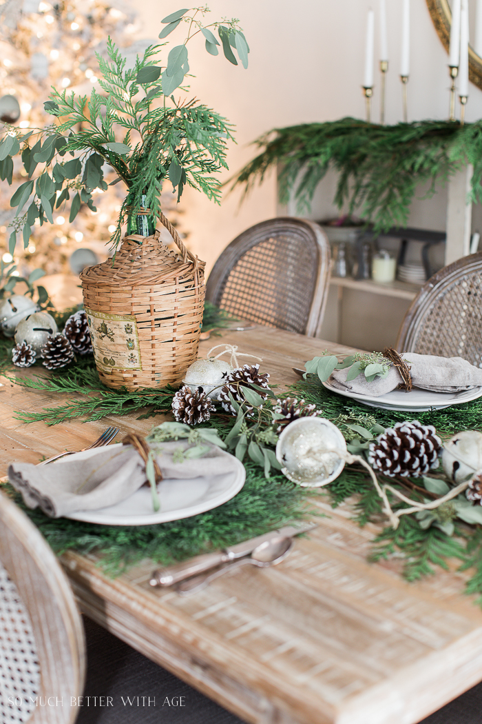 Cedar branches on the table with bells and pinecones.