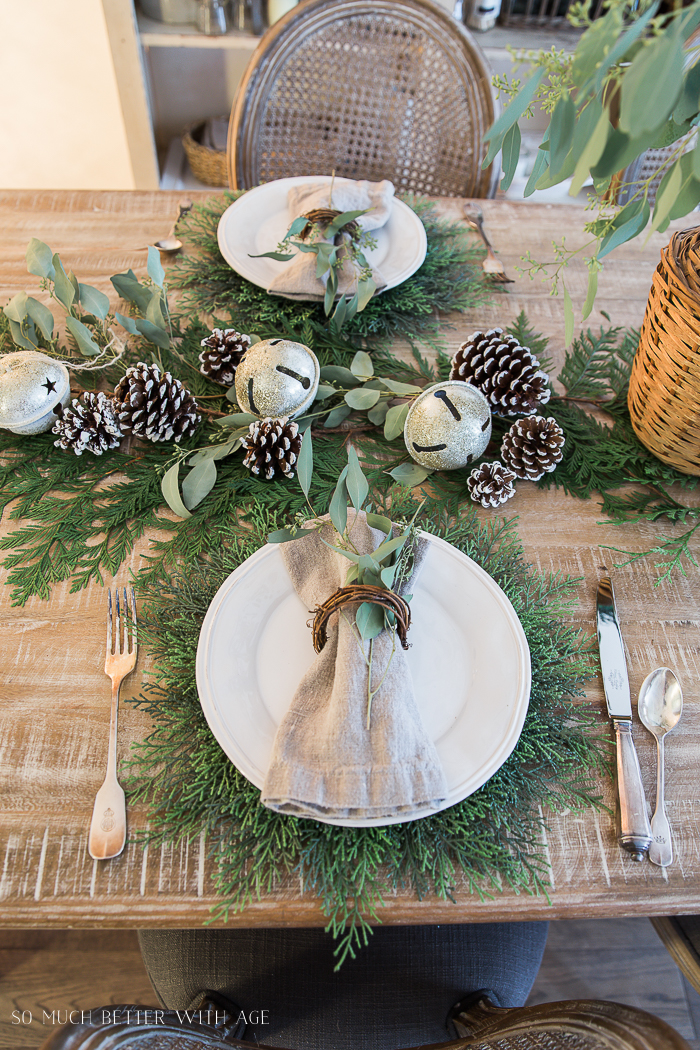 White plates, silver cutlery, evergreen, and pinecones on table.