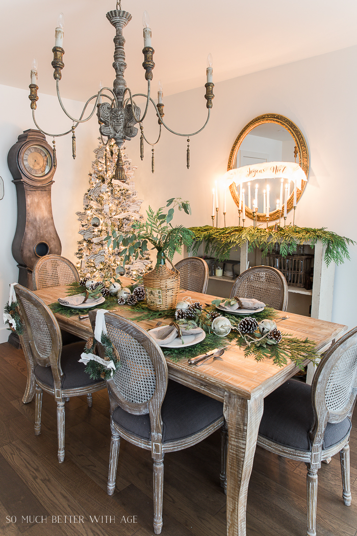 A wooden table set for Christmas with pine cones on it, evergreen on the table, mini wreaths hanging on the back of the chairs with white ribbon.