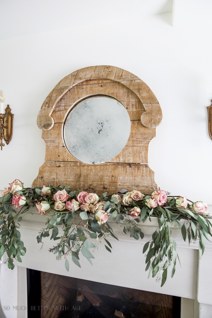 Rustic mirror with antique glass and roses and eucalyptus on the mantel.