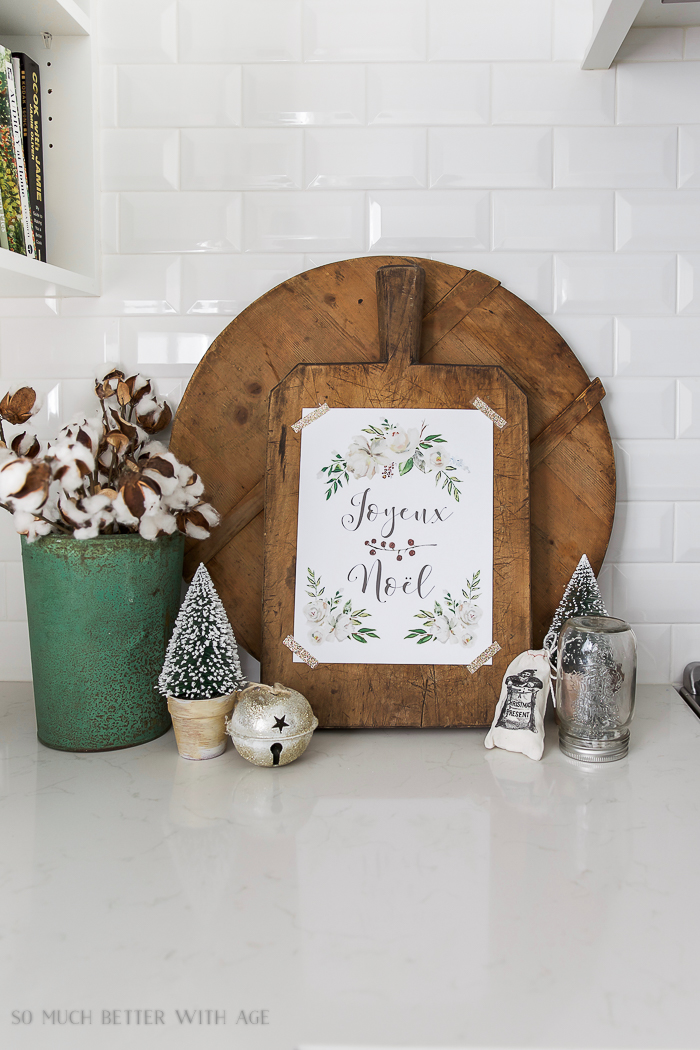 Joyeux Noel - Free Christmas Printable taped to a wooden bread board.
