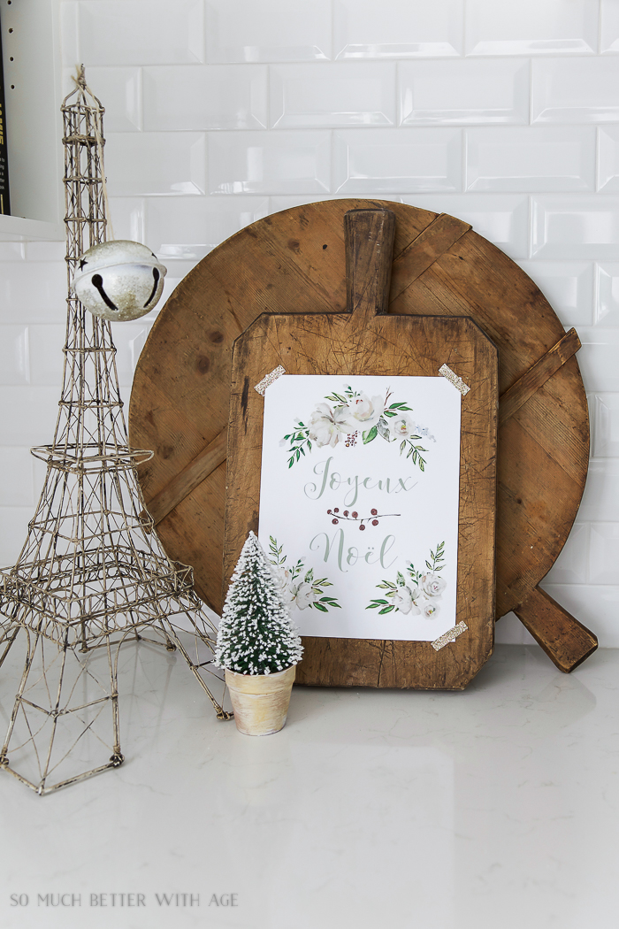 Joyeux Noel - Free Christmas printable on the bread board with a mini Christmas tree and an Eiffel Tower beside it.