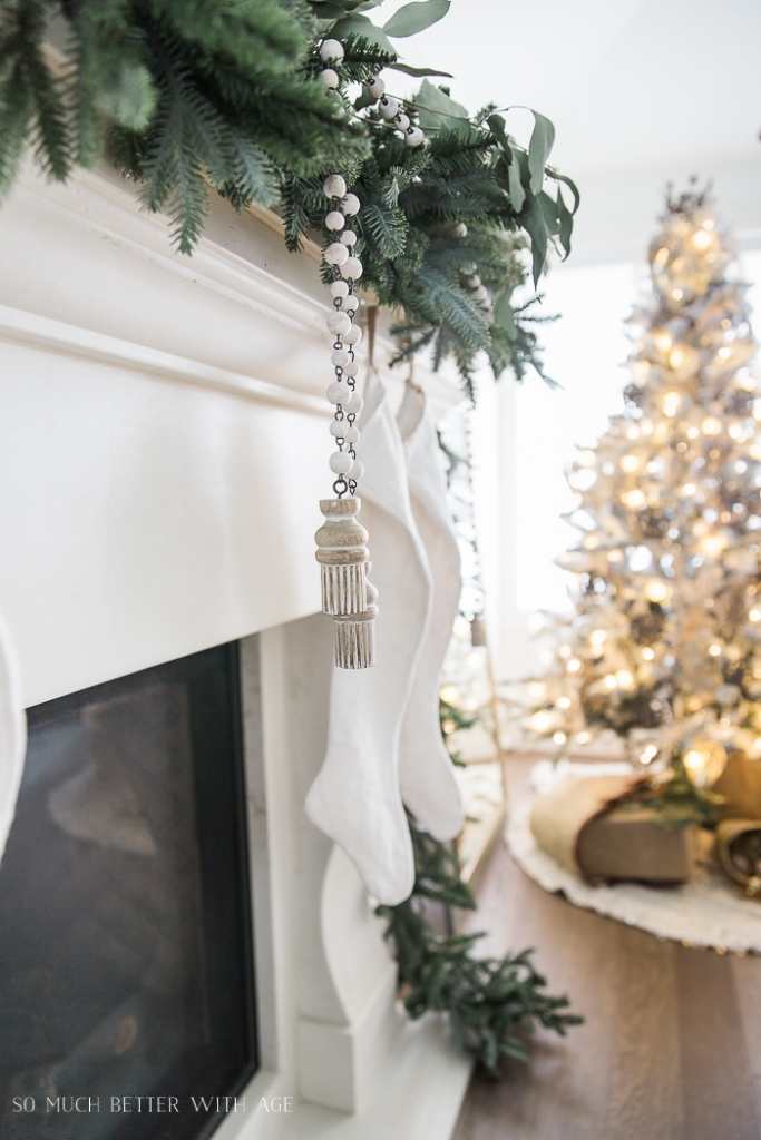 White fireplace mantel with evergreen and eucalyptus on it.