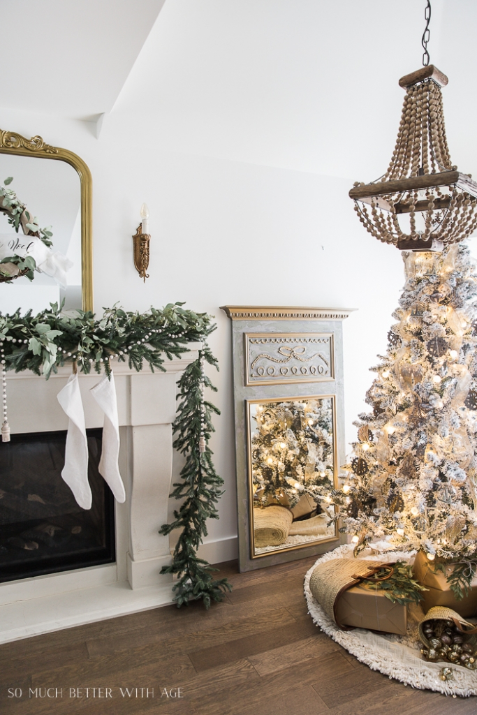 Gold and White Christmas tree with wrapped presents under the tree and eucalyptus and evergreen on the mantel.