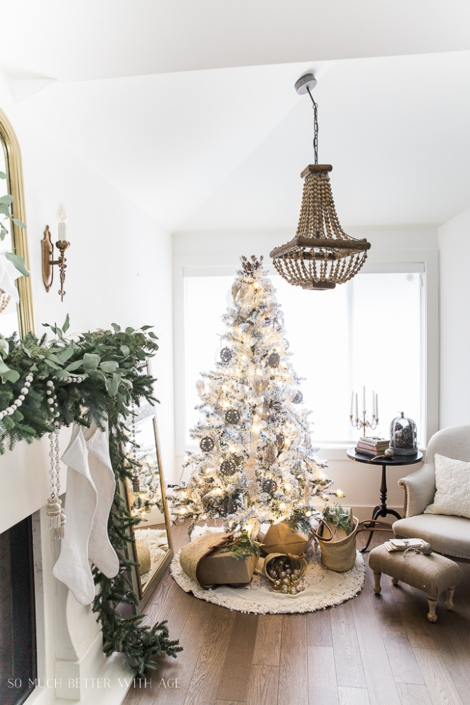 Living room with neutral armchair, side table with a glass cloche, Christmas tree and wooden beaded chandelier.