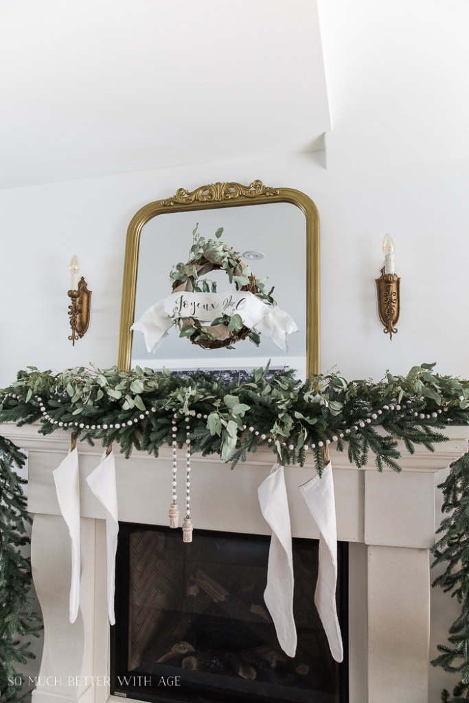 Gold mirror with Christmas wreath on it all above the evergreen and eucalyptus garland on the mantel.
