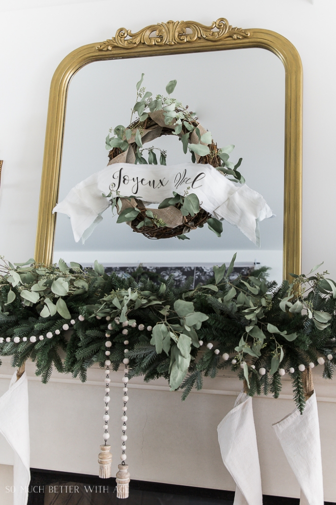Gold mirror on mantel with wreath on it and green garland hung over mantel.
