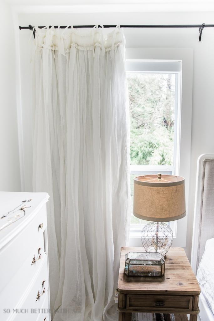 White curtains in bedroom beside night stand and lamp.
