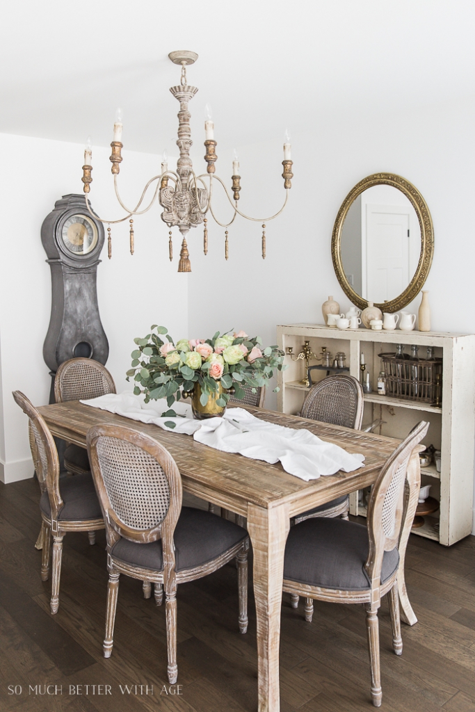 French chandelier in dining room with mora clock and gold mirror and big bouquet of roses and eucalyptus as centrepiece.