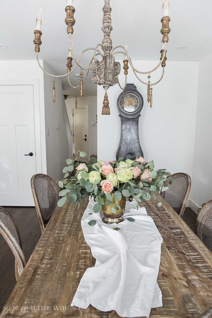 A beautiful ornate chandelier hanging above a wooden dining room table.