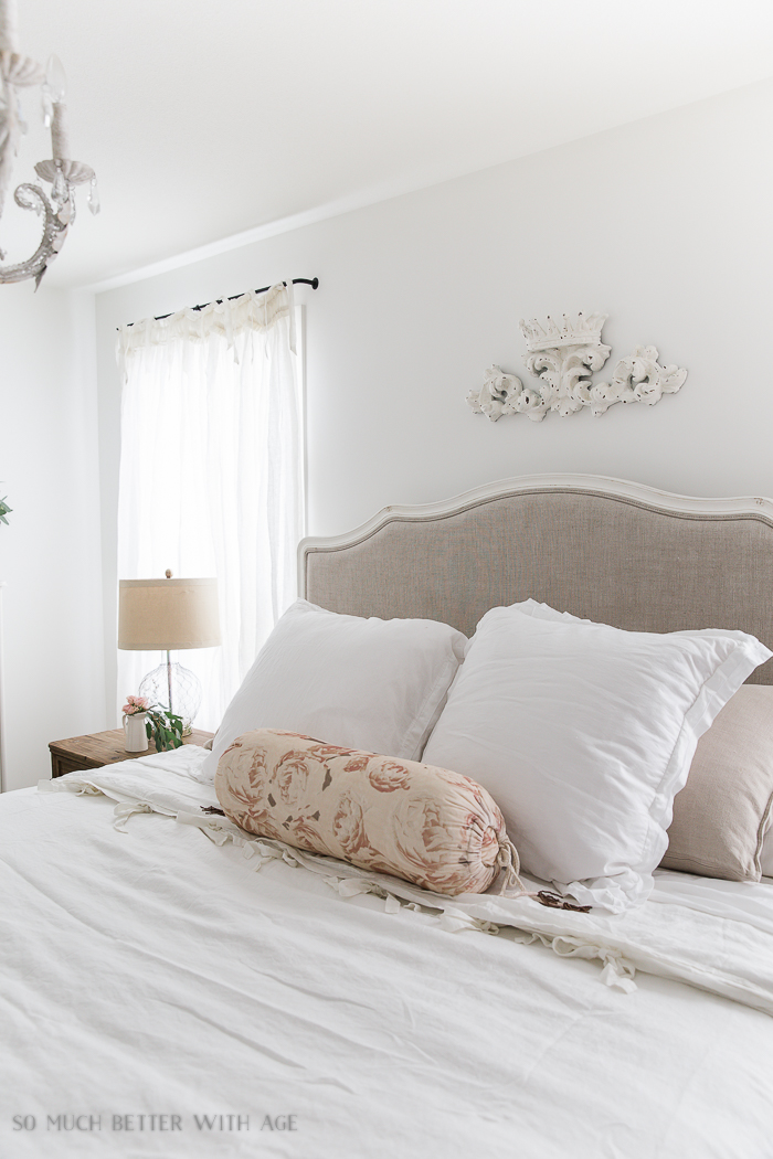 Beige neutral upholstered headboard with white pillows and a pink rose body pillow on white bedding.