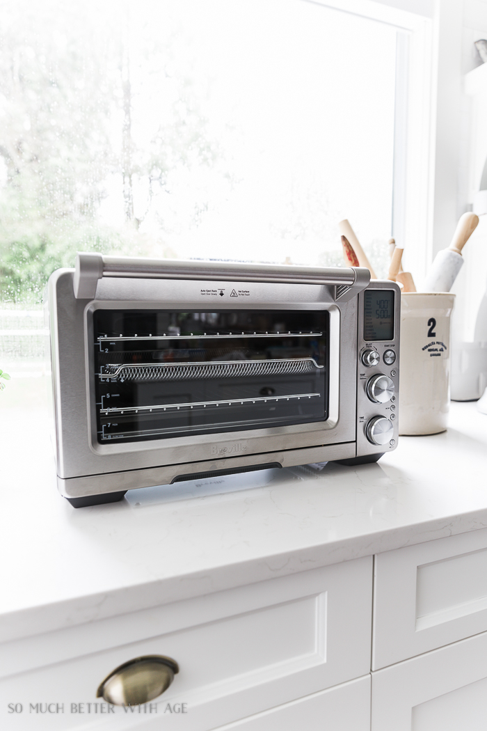 The Breville Smart Oven Air on the counter beside a crock with rolling pins.