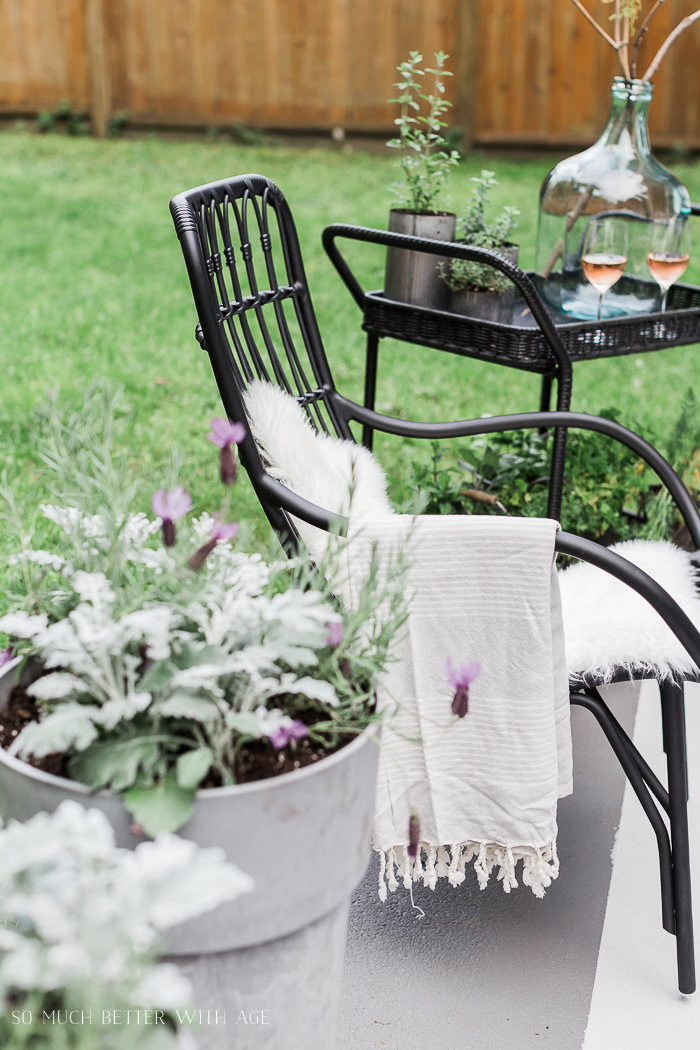 Outdoor seats with throw blanket draped over side.