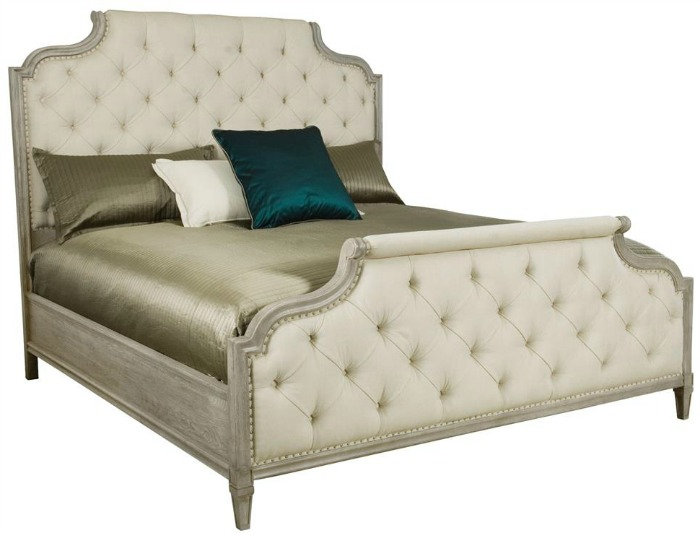 White tufted bed frame with silver bedding a turquoise pillow.