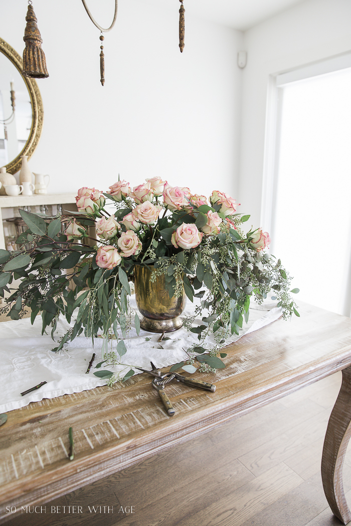 Roses and eucalyptus centrepiece on table.