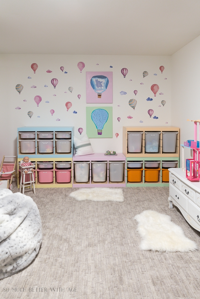 Playroom with pastel colored storage units and hot air balloon decals on wall.