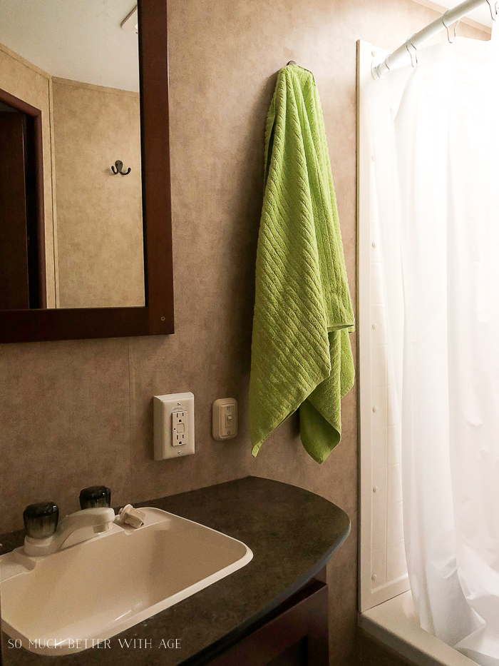 Green towel hanging on a hook in the RV bathroom.
