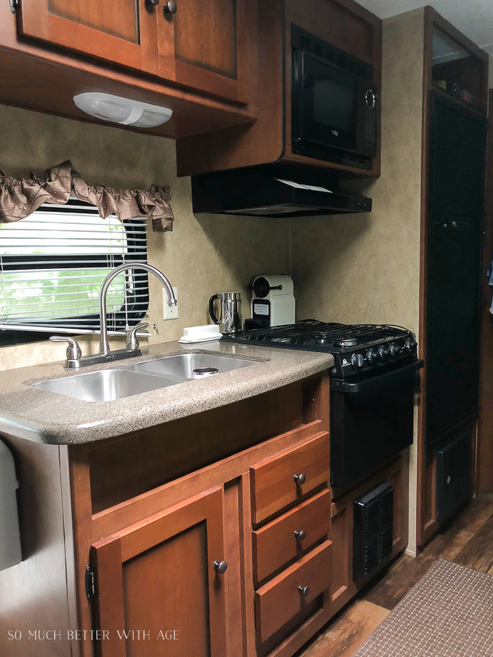 Interior of RV, a sink, stove, and microwave.