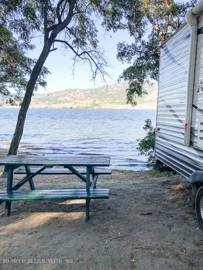 Picnic table and lake with RV.