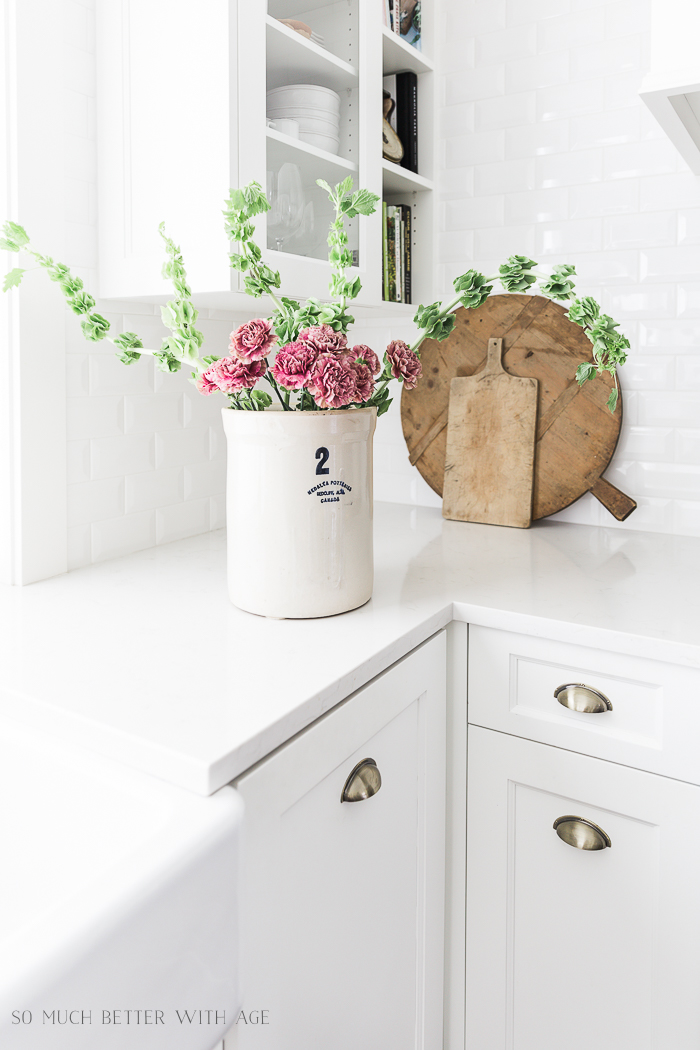 White Frech kitchen with crock on counter and pink and green flowers in crock.