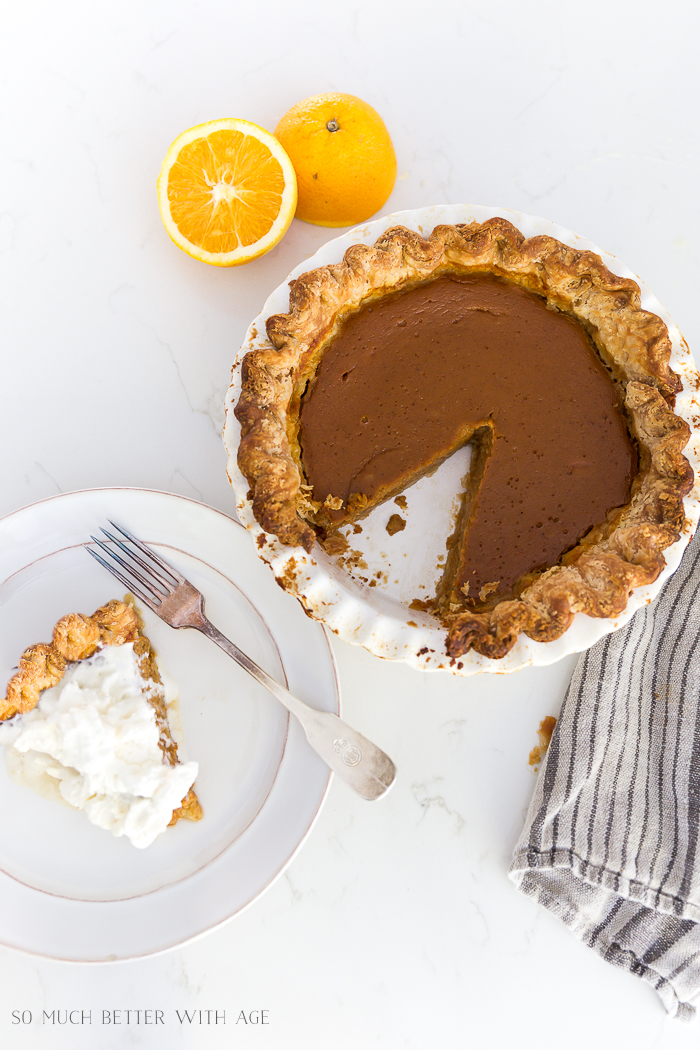Pumpkin pie in pie plate and also a slice on a white plate with whipping cream on top.