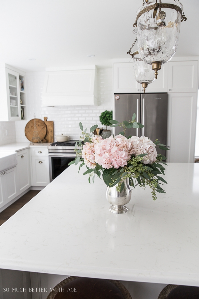 Pink peonies and eucalyptus in vase on large kitchen island.