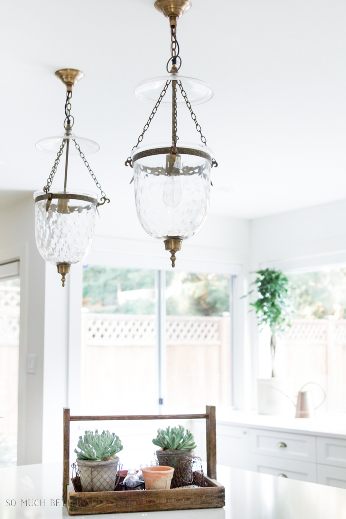 The urn lights in the all white neutral kitchen.