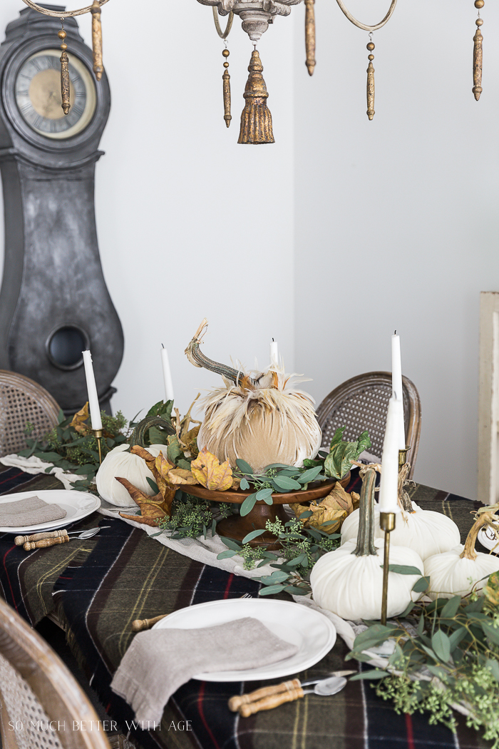 Velvet pumpkins and plaid tablecloth on table with white candles.