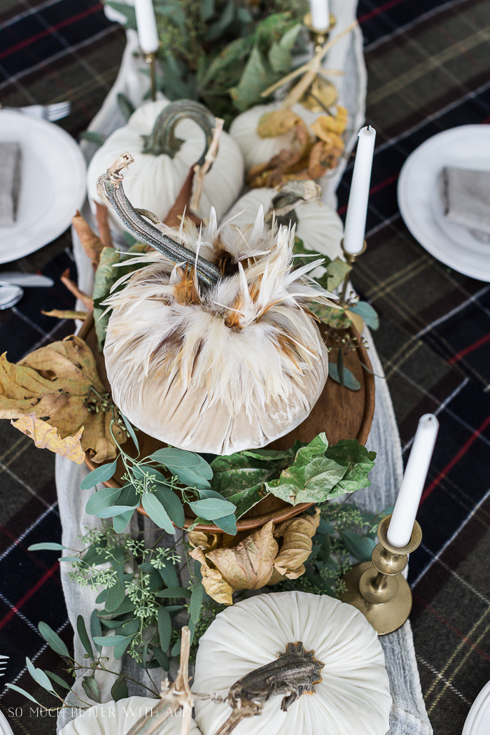 White velvet pumpkins with feathers on DIY centerpiece on table.