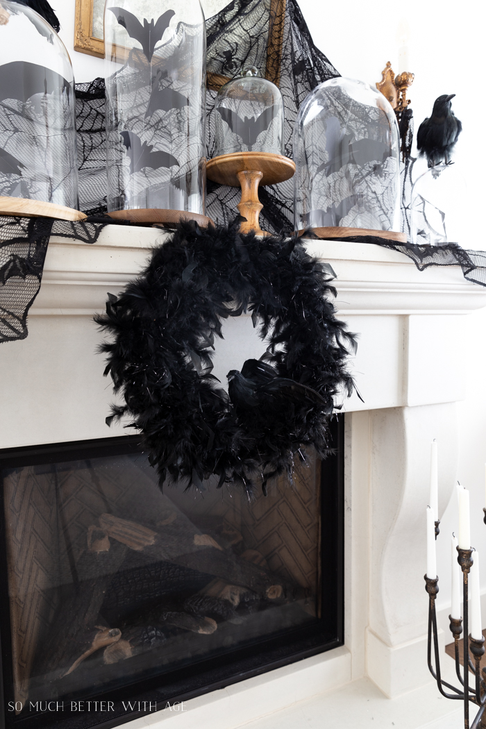 White mantel with black feathered wreath with a crow on it and crows in cloches.