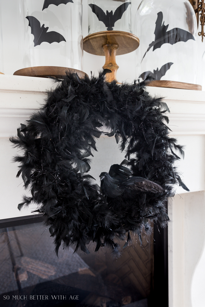 Bats flying in cloches on white fireplace mantel with black feathered wreath hanging below.