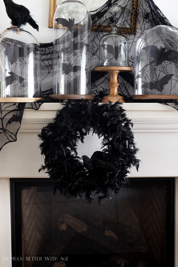 Fireplace mantel with black crow wreath hanging above it and a spider web behind it.