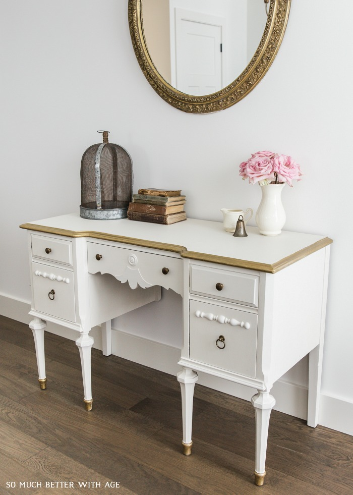 Gold mirror with white and gold desk and vintage accessories.