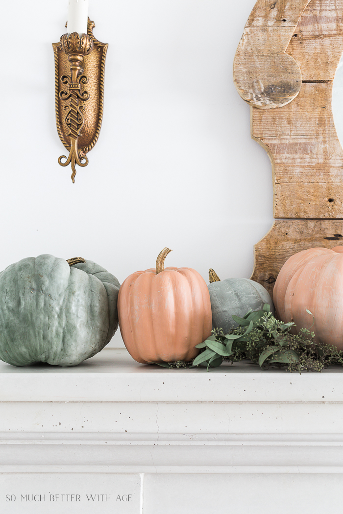 Four pumpkins in a sage green and soft orange on the mantel with eucalyptus.