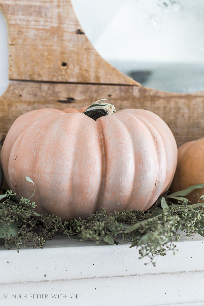 Painting Pumpkins in Muted Colors/pale orange pumpkin on the mantel with greenery.